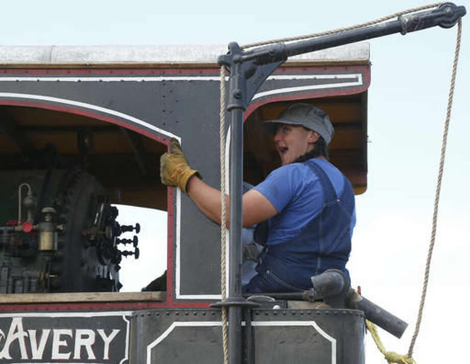 Jolene Streets shouts a greeting from her seat on an Avery steam engine tractor at the University of Wyoming's Powell Research and Extension Center near Powell, Wyo., on July 19, 2016. (Ilene Olson /The Powell Tribune via AP)