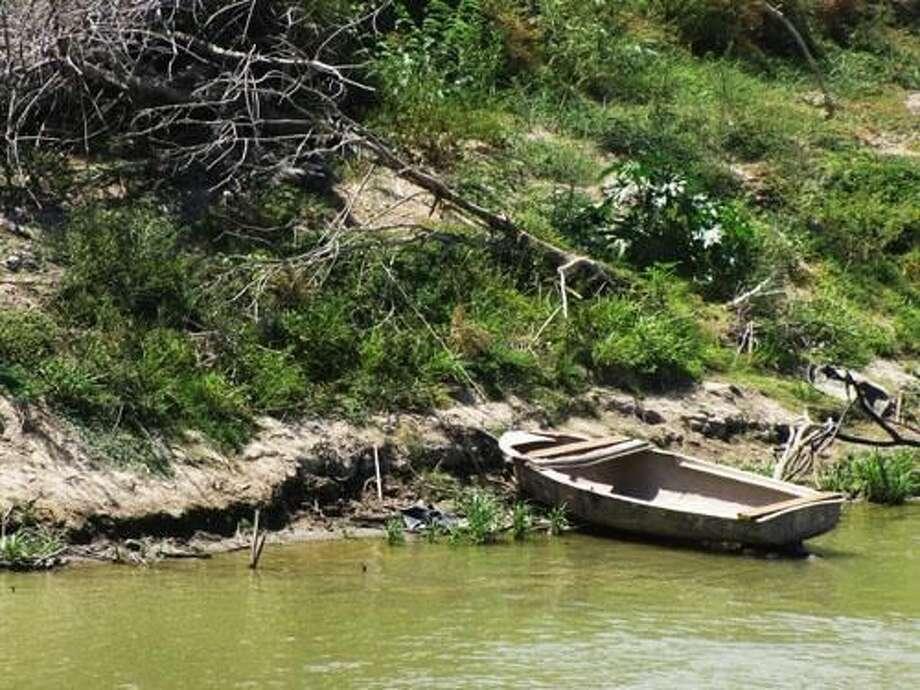 En la ribera mexicana se observa una lancha abandonada, el 9 de agosto. Autoridades del Condado de Zapata dicen que esta área al norte de San Ygnacio es frecuentada por traficantes, ya sea de humanos o narcóticos, y que pudo ser utilizada para ese fin.