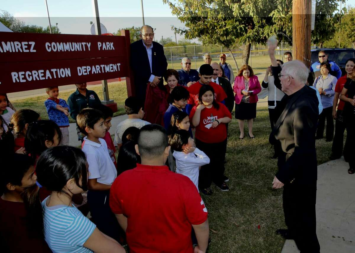Former councilman and community activist Juan Ramirez is accompanied by family and friends as Father Bill Davis blesses the site of the marker renaming the former El Cuatro Neighborhood Community Park to the Juan Ramirez Community Park, Wednesday afternoon. (Photo by: Victor Strife