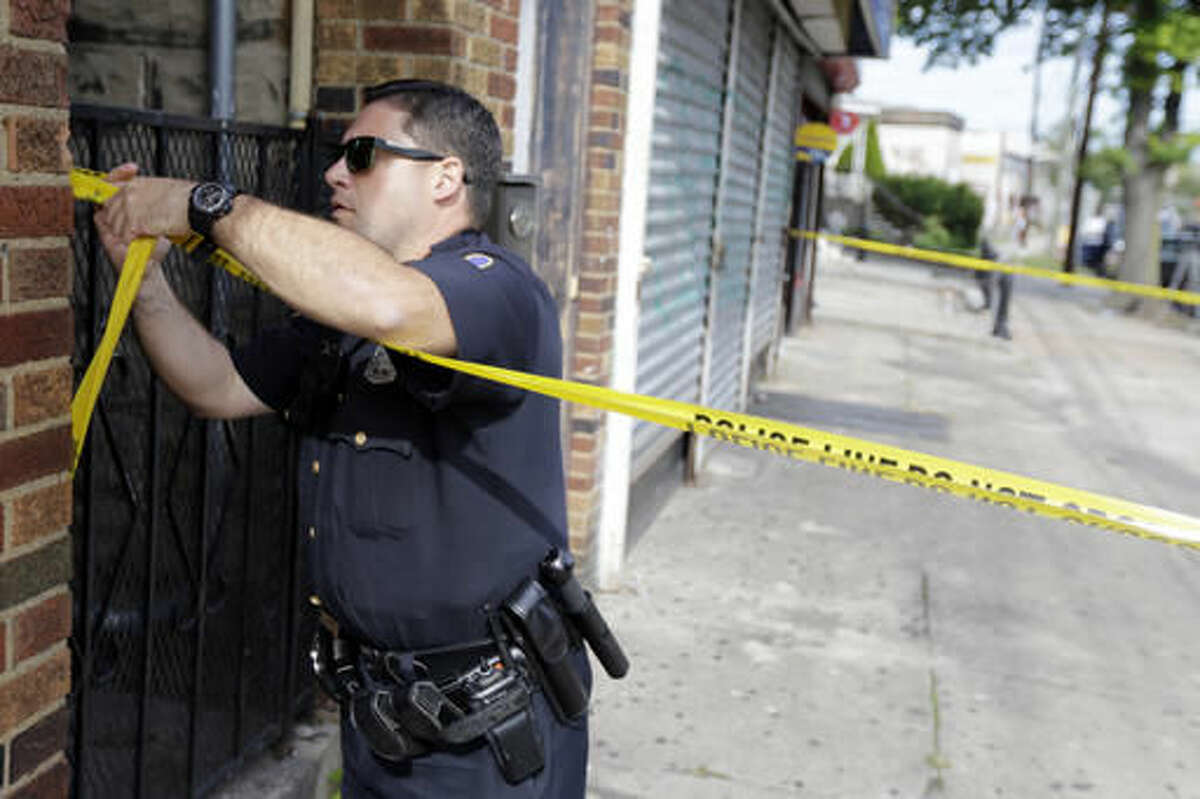 A police officer ties tape around the First American Fried Chicken restaurant, Wednesday, Sept. 21, 2016, in Elizabeth, N.J. The Elizabeth establishment and the apartment above are tied to Ahmad Khan Rahami, who was arrested as a suspect in the weekend bombings in New York and New Jersey. (AP Photo/Julio Cortez)