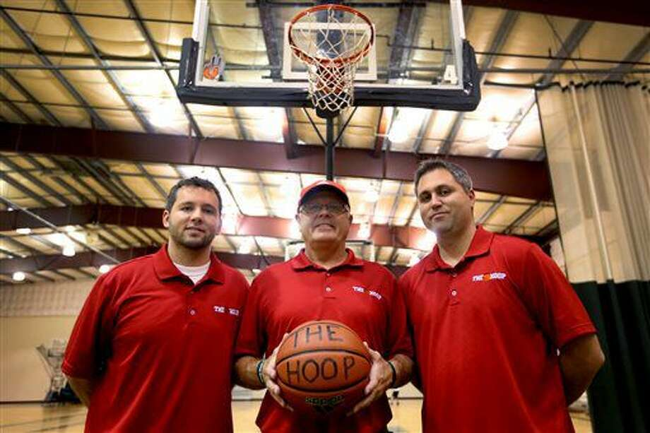 In this Wednesday, Sept. 7, 2016 photo, Price Johnson, center, and his sons Dane Johnson, left, and James Johnson, right, own and operate The Hoop, a competitive basketball training facility in Salem, Ore. The Hoop in Salem is a full fitness center. It is rented for various activities including volleyball, roller skating and wedding receptions. (Anna Reed/Statesman-Journal via AP)