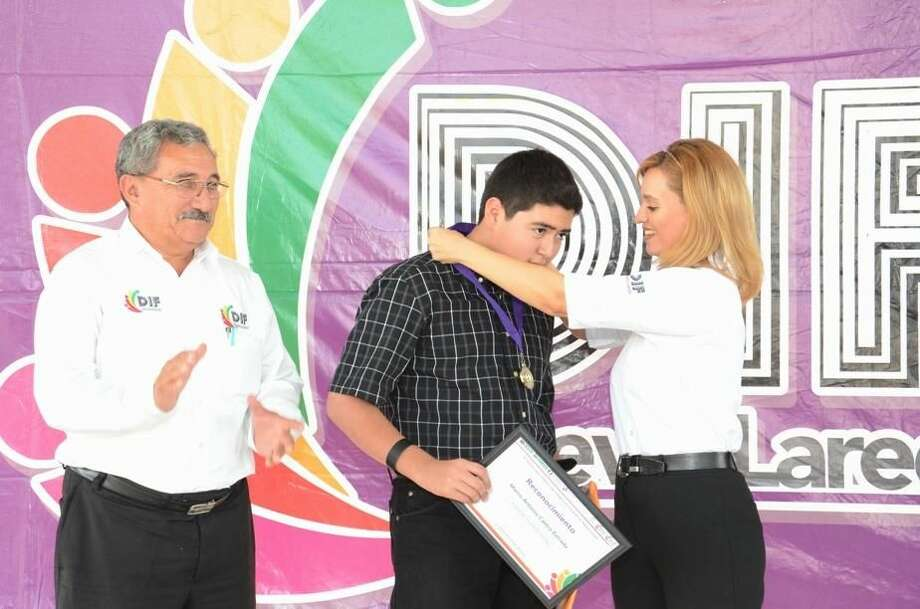 Marco Antonio Castro Estrada recibe una medalla de manos de la Presidenta del Sistema DIF-Nuevo Laredo, Martha Alicia Aldapa. A la izquierda, el maestro de música Cuauhtémoc Ibarra Paul. (Foto de cortesía)