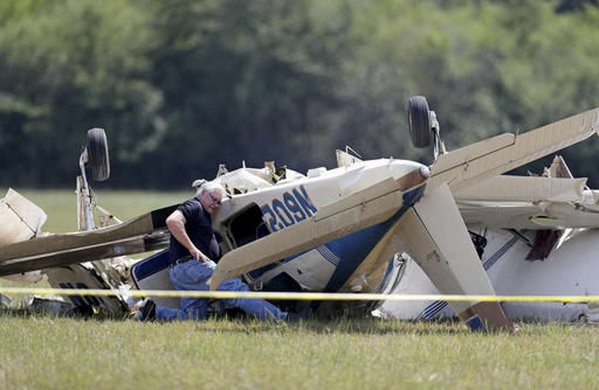 An investigator looks at the debris of a plane crash at West Georgia Regional Airport in Carrollton, Ga., Wednesday, Sept. 7, 2016. Carroll County Fire Chief Scott Blue says two single-engine planes may have been trying to land at the same time when they collided at the small airport in western Georgia leaving three people dead. (AP Photo/David Goldman)