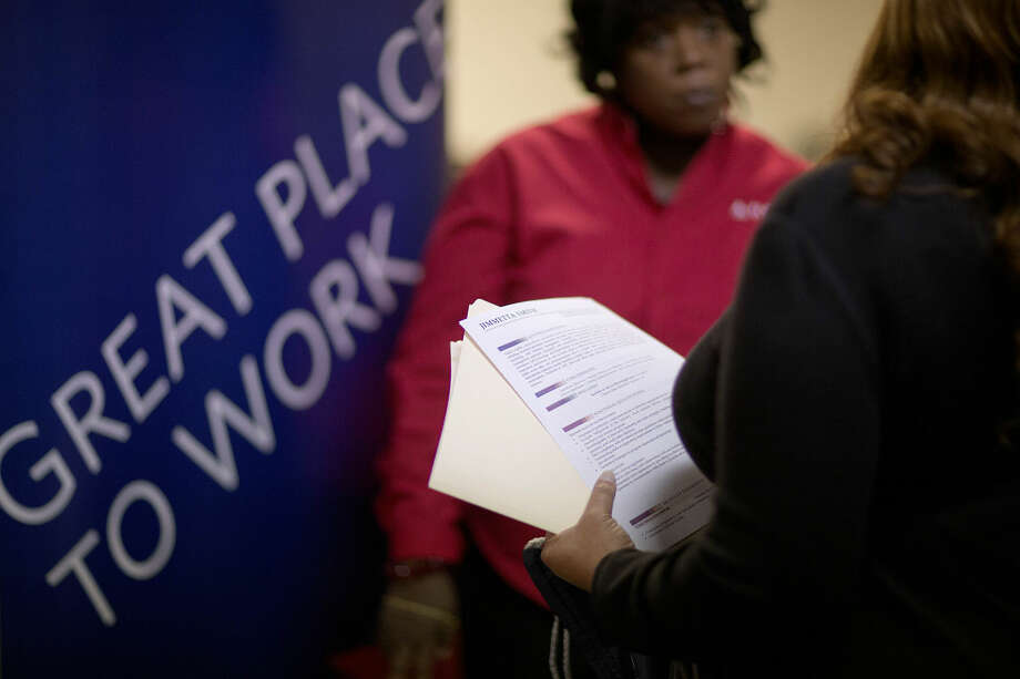 In this Thursday, Nov. 14, 2013, file photo, Jimmetta Smith, of Lithonia, Ga., right, the wife of a U.S. Marine veteran, holds her resume while talking with Rhonda Knight, a senior recruiter for Delta airlines, at a job fair for veterans and family members at the VFW Post 2681, in Marietta, Ga. The Labor Department issues the November jobs report on Friday, Dec. 6, 2013. (AP Photo/David Goldman, File)