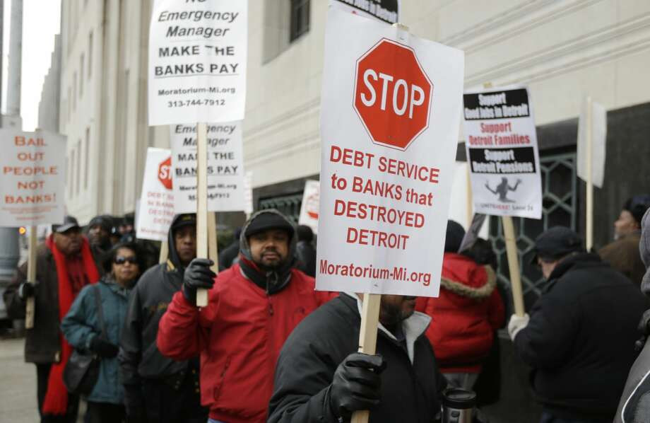 Detroit city workers and supporters protest outside the federal courthouse in Detroit while awaiting the bankruptcy decision, Tuesday, Dec. 3, 2013. A judge is expected to announce Tuesday if the city is to become the biggest city in U.S. history to enter bankruptcy. (AP Photo/Carlos Osorio)