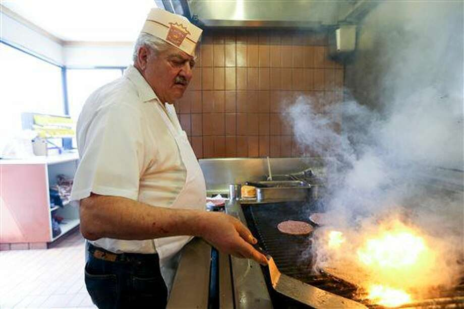 ADVANCE FOR THE WEEKEND OF SEPT. 17-18 AND THEREAFTER - In a Friday, Aug. 5, 2016 photo, John Katzourakis works the broiler at Crown Burgers in Salt Lake City. John and Rula and their brothers, sisters, nephews and nieces own and operate seven restaurants, six of them in Salt Lake Valley. (Spenser Heaps/The Deseret News via AP)