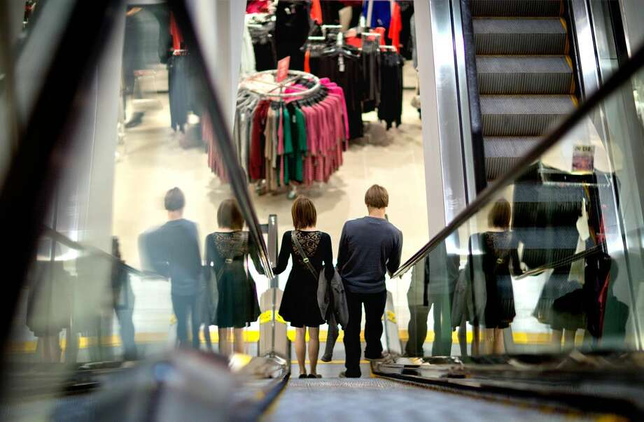 In this Wednesday, Dec. 12, 2012, photo, a couple descend an escalator while shopping at an H& M store, in Atlanta. U.S. consumer confidence tumbled in December, driven lower by fears of sharp tax increases and government spending cuts set to take effect next week. The Conference Board said Thursday that its consumer confidence index fell this month to 65.1, down from 71.5 in November. That's second straight decline and the lowest level since August. (AP Photo/David Goldman)