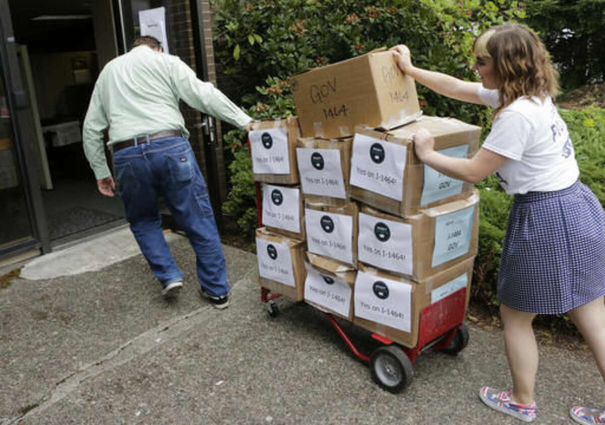 FILE - In this July 8, 2016, file photo, supporters of a proposed campaign finance reform ballot measure arrive to turn in boxes of signed petitions in Olympia, Wash. Washington voters will soon decide whether or not to make the most sweeping changes to the state's campaign finance system in decades. (AP Photo/Rachel La Corte, File)