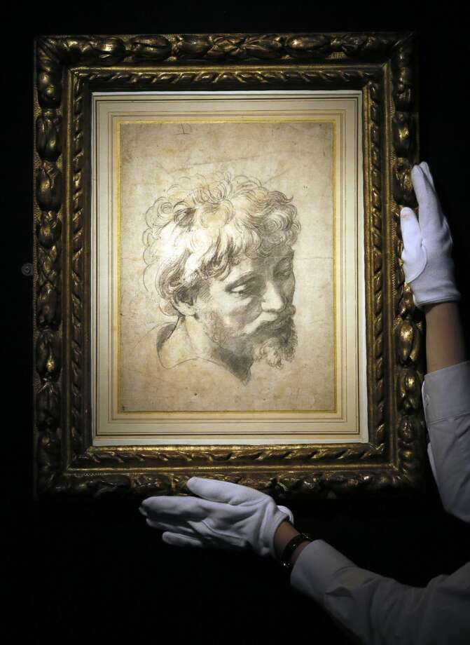 A Sotheby's employee adjusts a drawing by Raffaello Sanzio, otherwise known as Raphael called 'Head of an Apostle', a Renaissance masterwork, during a press viewing in London, Friday, Nov. 30, 2012. The drawing estimated at 10-15 million pounds (16-24 million US Dollars) will go on sale in the evening sale of Old Master Paintings and Drawings on Dec. 5 in London. (AP Photo/Kirsty Wigglesworth)