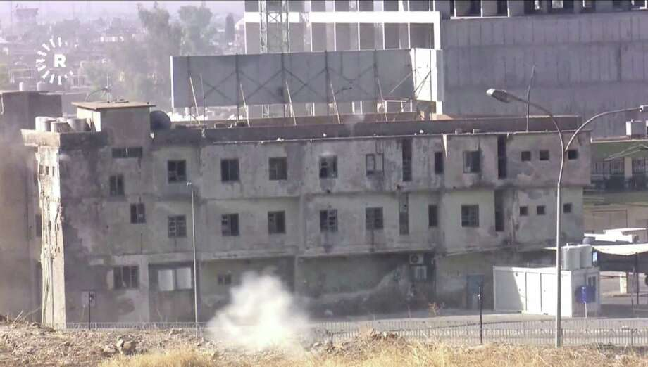 In this image made from video, smoke rises from a building where two militants are believed to be holed up, according to Rudaw TV, in Kirkuk, Iraq, Friday, Oct. 21, 2016. Militants armed with assault rifles and explosives attacked targets in and around the northern Iraqi city of Kirkuk early on Friday in an assault quickly claimed by the Islamic State group and likely aimed at diverting authorities' attention for the battle to retake IS-held Mosul. (Rudaw TV via AP) ORG XMIT: TKTT802 / Rudaw TV