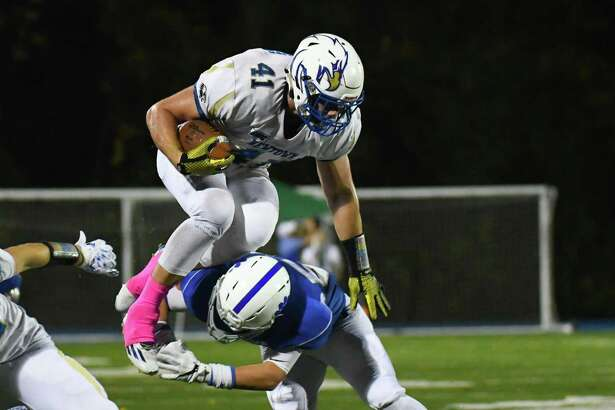 Ben Mason (41) attempts to leap over a tackle during a game against Bunnell Friday night at Bunnell High School in Stratford. Newtown ralleid for a 35-34 victory.