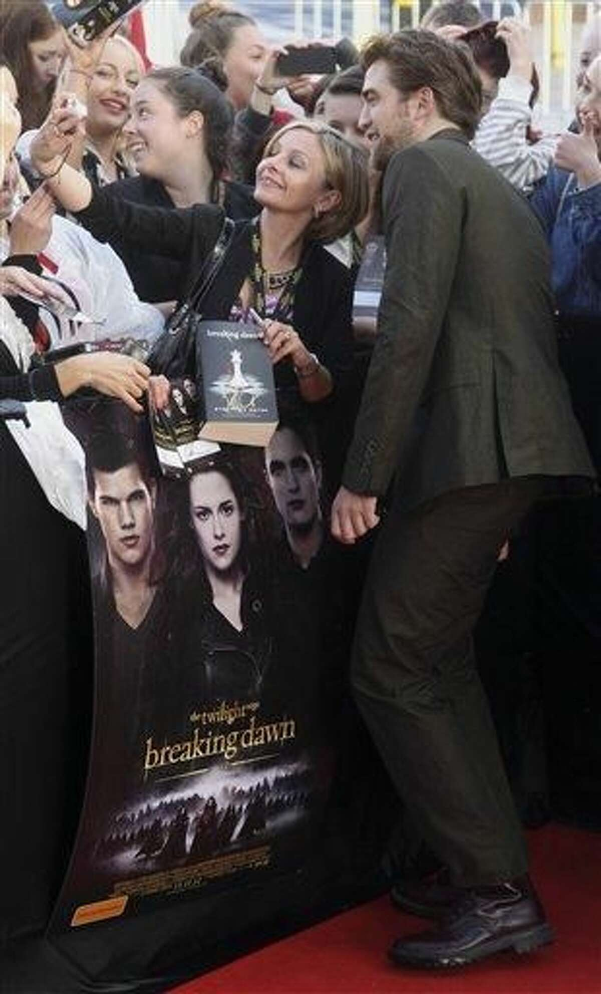 FILE - This Oct. 22, 2012 file photo shows British actor Robert Pattinson, right, having his photo taken with fans upon arrival for an exclusive fan event for the final chapter of the Twilight Saga