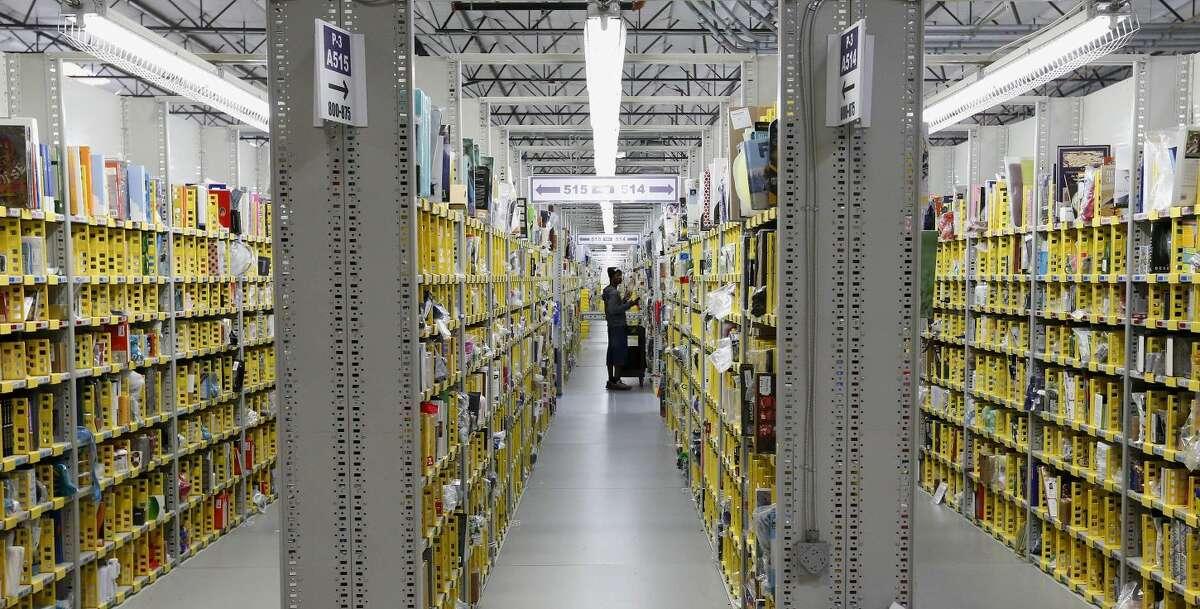 An Amazon.com employee stocks a shelf at an Amazon.com Fulfillment Center on