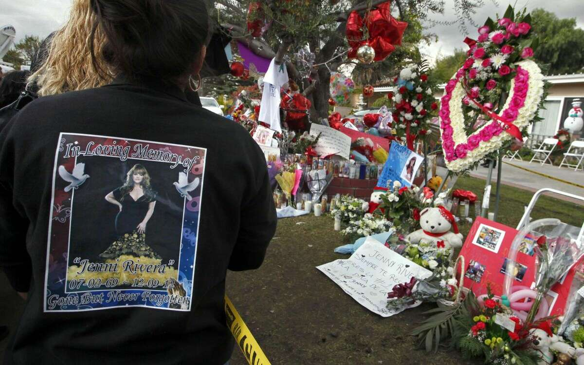 Mourners stand outside the home of Jenni Rivera's family in Lakewood Calif., Friday, Dec. 14, 2012. Three brothers of Rivera, a Southern California native, accompanied the Latin star's remains on a Thursday night flight from Mexico to the Long Beach airport. Escorted by police, her casket was then driven to a Long Beach mortuary, where dozens of fans waited. Other fans gathered outside her mother's home in Lakewood, where well-wishers have left a memorial of balloons, candles and flowers. (AP Photo/Nick Ut)