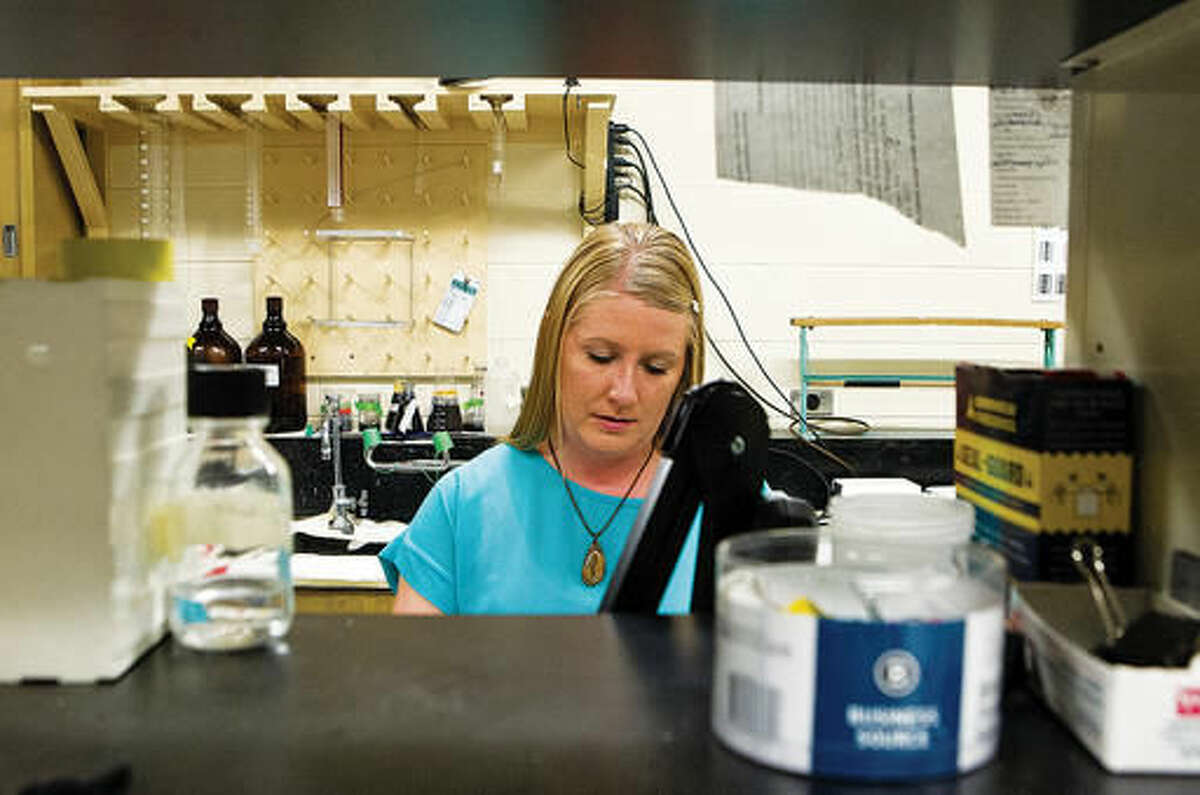 In this Aug. 18, 2016 photo, Tasha Bauman, a forensic analyst at the Game and Fish Wildlife Forensic Laboratory, works in a laboratory at the University of Wyoming in Laramie, Wyo. Bauman uses a host of sophisticated instruments to identify species, discern their gender and figure out how many animals are represented. (Shannon Broderick/Laramie Daily Boomerang via AP)