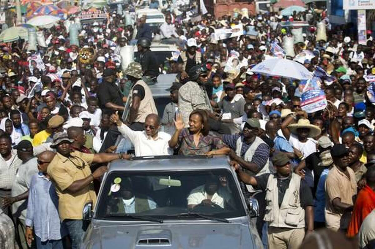 """In this Sept. 21, 2016 photo, Haiti's former President Jean-Bertrand Aristide, left, waves to supporters as he campaigns with presidential candidate Maryse Narcisse, of the Fanmi Lavalas political party, in Port-au-Prince, Haiti. """"He's the king of kings! Seeing him on the streets is like being in paradise,"""" Port-au-Prince resident Jhony Narcisse said as he jogged to keep up with Aristide's motorcade during the rally. Haiti will hold elections on Oct. 9. (AP Photo/Dieu Nalio Chery)"""