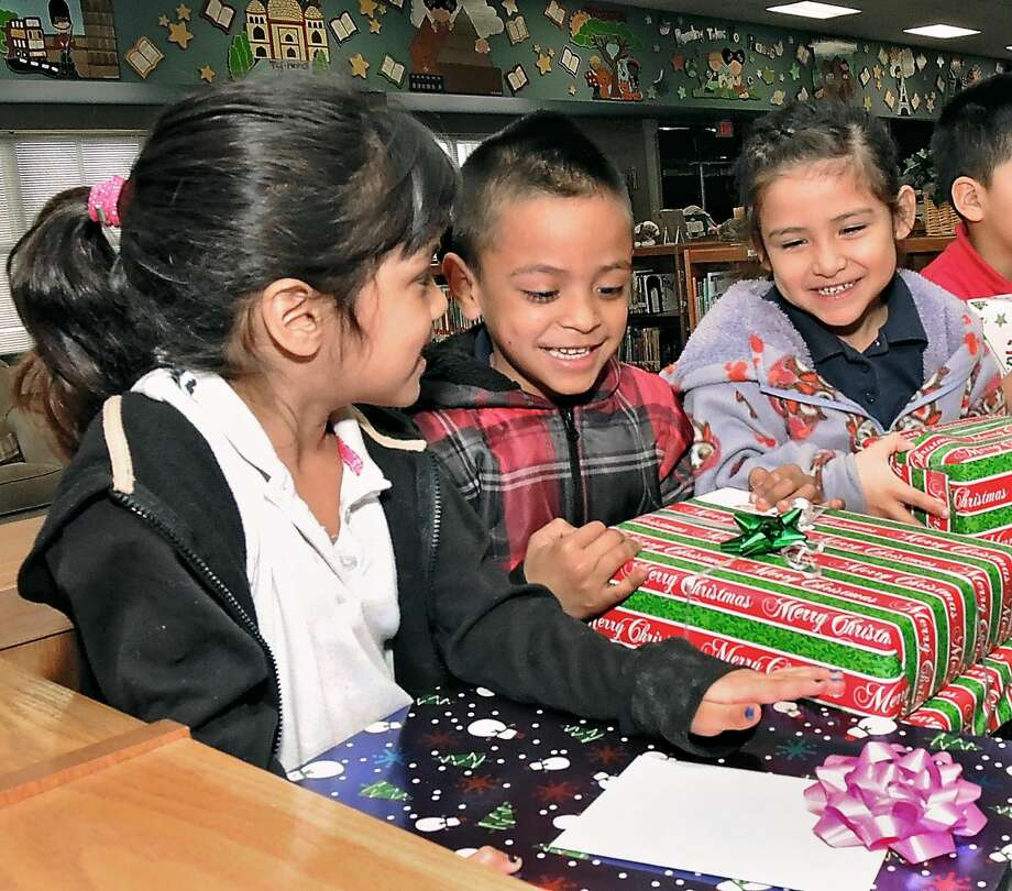 Season for givingSanto Niño Elementary School students Reana Rodriguez, left, Rigo Rodriguez and Marisol Soto smile as they look at Christmas presents presented to them and other students Thursday by members of the First United Methodist Church. (Photo by Cuate Santos/Laredo Morning Times)