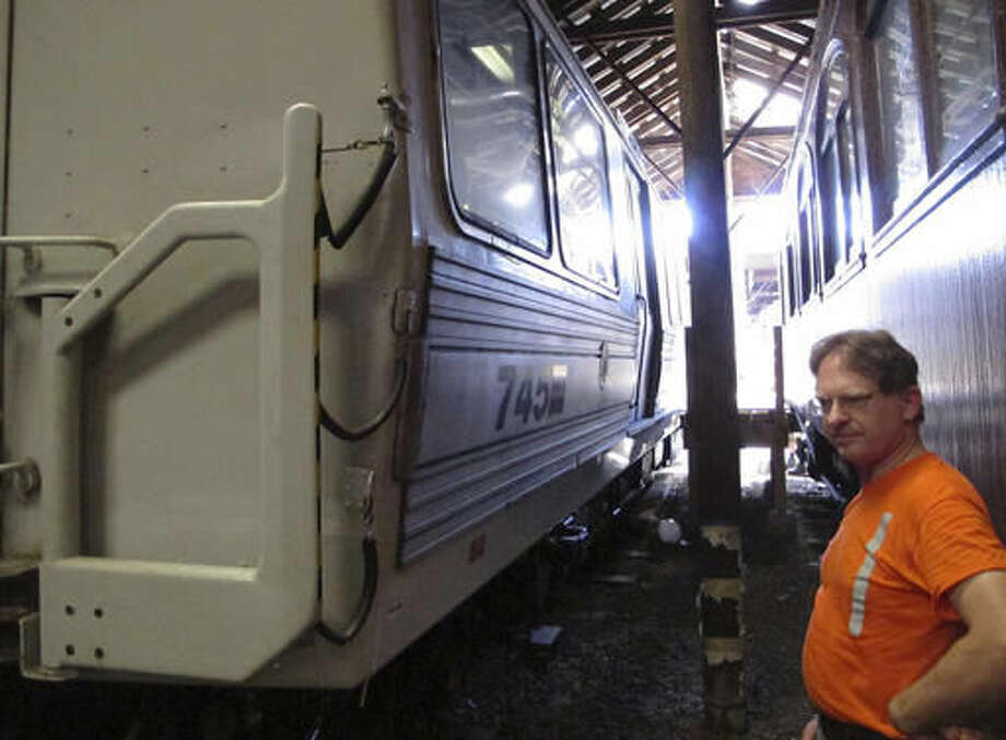 In this Aug. 17, 2016 photo, Conrad Misek, a conservator at the Shore Line Trolley Museum, stands outside PATH car 745 at the museum in East Haven, Conn. The subway car was beneath the World Trade Center in New York during the terrorist attack on Sept. 11, 2001. The museum will dedicate and open to the public an exhibit featuring the car on Sept. 11, 2016. (AP Photo/Dave Collins)