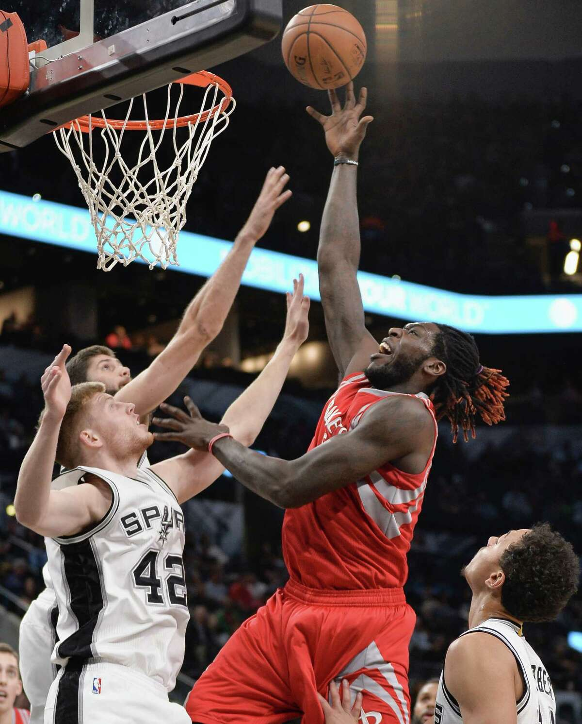 Houston Rockets forward Montrezl Harrell, center, shoots against San Antonio Spurs' Davis Bertans (42), of Latvia; Bryn Forbes, right; and Patricio Garino, of Argentina, during the first half of a preseason NBA basketball game, Friday, Oct. 21, 2016, in San Antonio. (AP Photo/Darren Abate)