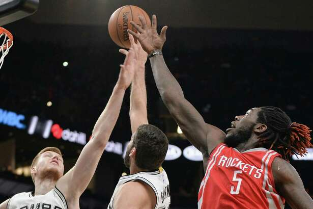 Houston Rockets forward Montrezl Harrell (5) chases the ball against San Antonio Spurs forward Davis Bertans (42), of Latvia, and Spurs guard Patricio Garino, of Argentina, during the first half of a preseason NBA basketball game, Friday, Oct. 21, 2016, in San Antonio. (AP Photo/Darren Abate)