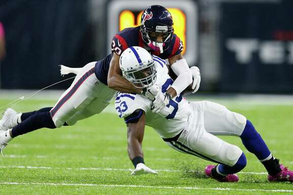 Kevin Johnson, top, makes the Colts' Robert Turbin one of his 10 tackles Sunday. But the Texans cornerback is out for the year after breaking a foot in the game.