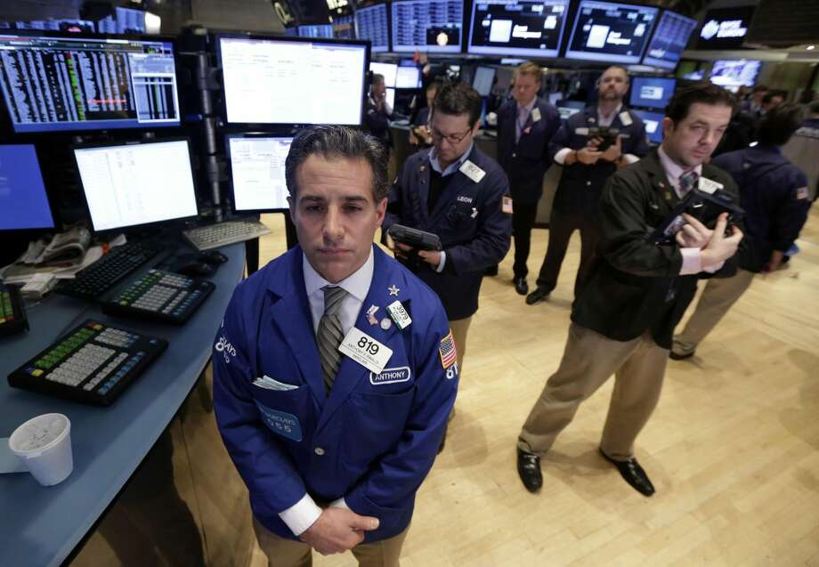 Traders on the floor of the New York Stock Exchange observe a moment of silence for the death of Nelson Mandela before the opening bell, Friday, Dec. 6, 2013. Mandela, South Africa's first black president, died Thursday after a long illness. He was 95. (AP Photo/Richard Drew)