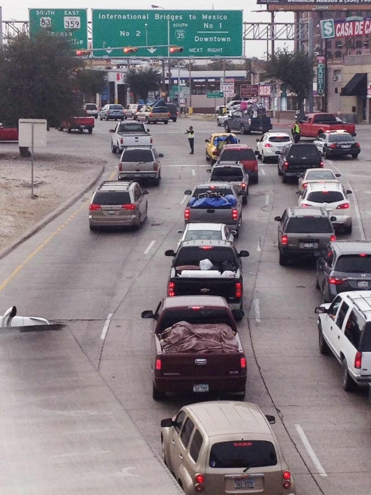 Laredo police officers direct traffic at Victoria Street and IH 35 Friday morning as paisanos make their way into Mexico Friday. (Photo by: Cuate Santos