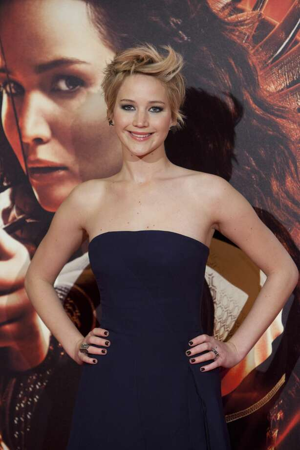 """FILE - In this Nov. 13, 2013 file photo, US actress Jennifer Lawrence poses for the photographers during the Spain premiere of the movie """"The Hunger Games: Catching Fire"""" at Callao Cinema in Madrid, Spain. Lawrence edged out Miley Cyrus by one vote in The Associated Press' annual survey of its newspaper and broadcast members and subscribers for Entertainer of the Year. (AP Photo/Abraham Caro Marin, File)"""