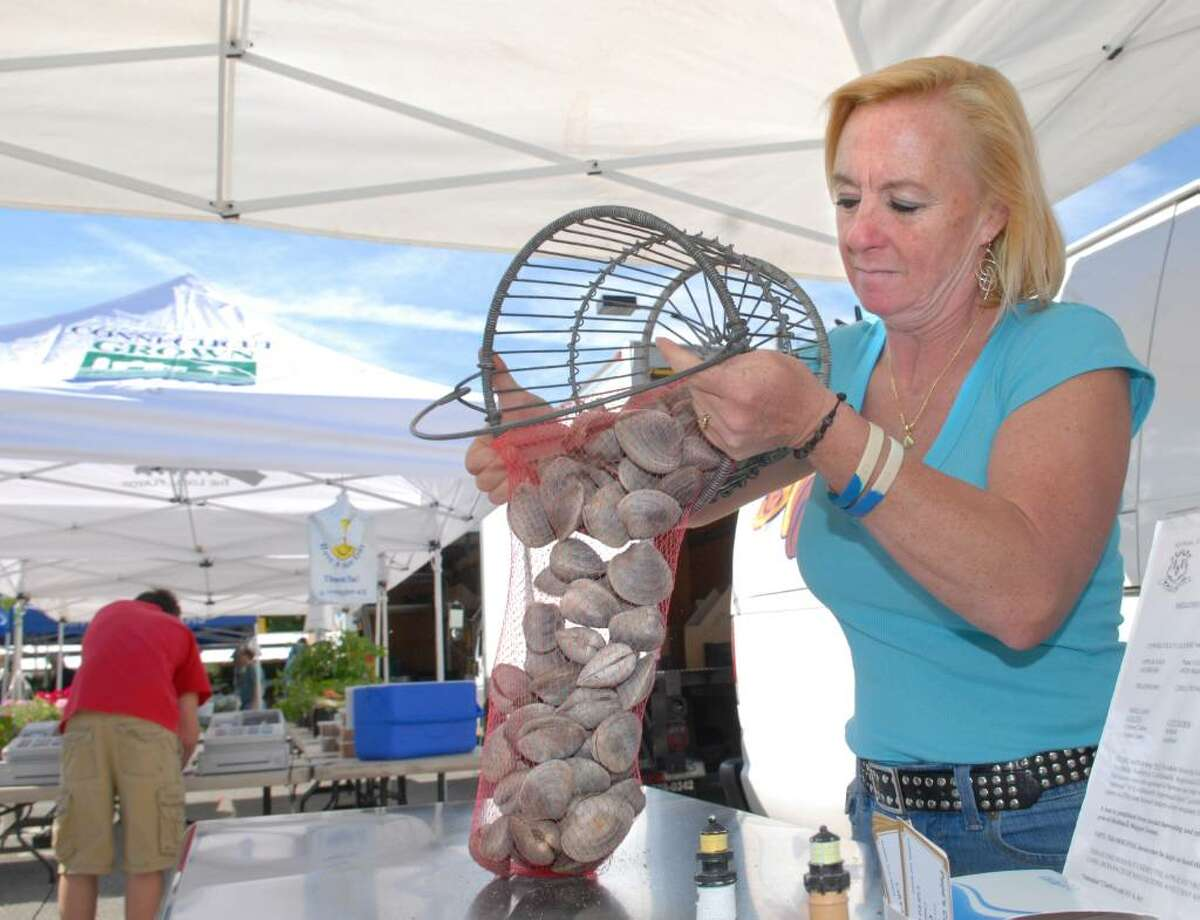 Laurie Popadic of Pepe's Cream of the Crop Shellfish Farm of Milford, Conn., loads littleneck clams into a plastic mesh bag for sale during the opening day of the Greenwich Farmers Market in the Horseneck public parking lot, Greenwich, Saturday morning, May 15, 2010. Popadic said a bag of 100 littleneck clams goes for $40.