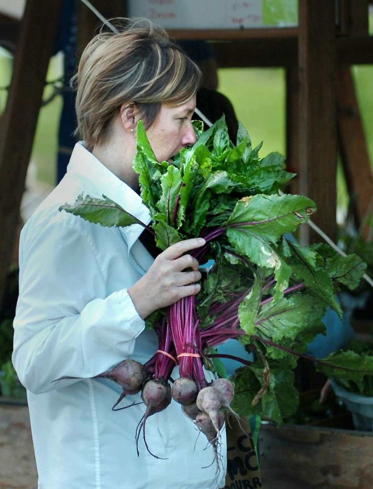 Anja Vaisanen of Greenwich checks the freshness of the beets she was purchasing from Gazy Brothers Farm of Oxford, Conn., by smelling them during the opening day of the Greenwich Farmers Market in the Horseneck public parking lot, Greenwich, Saturday morning, May 15, 2010.