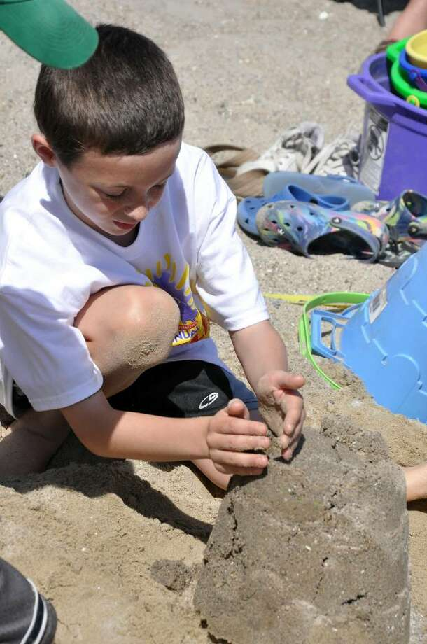 Nicholas Durkin, 9, of Westport, forms part of a castle during the ninth annual Castles in the Sand sandcastle build-a-thon at Compo Beach on Saturyda, May 15, 2010. Photo: Amy Mortensen / Connecticut Post