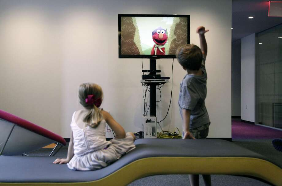 "In this Sept. 5, 2012, photo, from left, Zoe Shyba, 3, left, and Aidan Lain, 7, play ""Kinect Sesame Street TV"" at the Sesame Street Workshop in New York. ""Kinect Sesame Street TV."" (AP Photo/Mark Lennihan)"