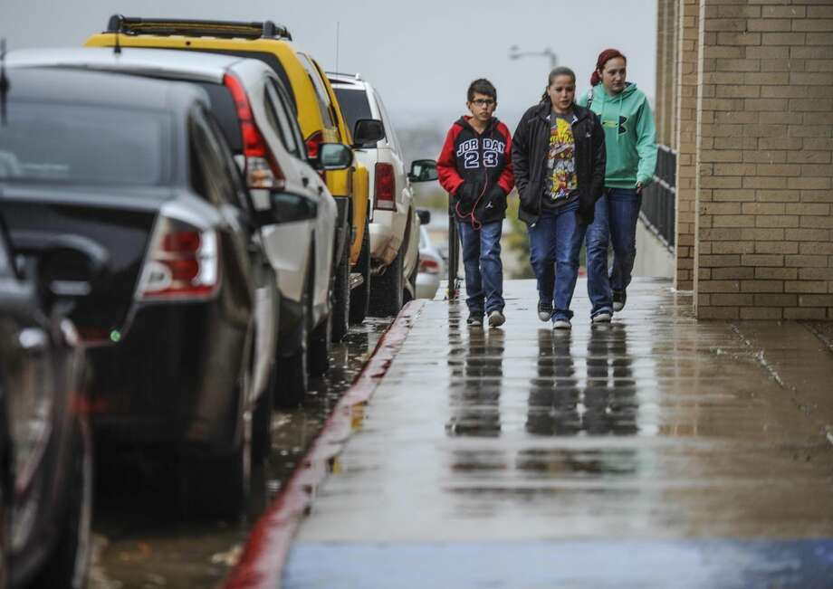 Basketball fans walk in the drizzly weather toward the United South High School gymnasium to watch the basketball game of United South against Nixon High School on Tuesday afternoon. Temperatures are expected to rise New Year's Day and into the weekend. (Photo by Danny Zaragoza/Laredo Morning Times)