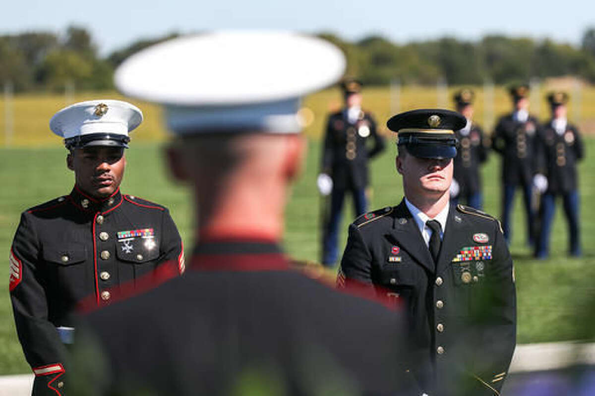 Marine Sgt. Demaidre Travis, left, and Army Sgt. Taylor Siebrandt, right, stand at attention as the brand-new Omaha National Cemetery holds its first burials as four veterans are buried with full honors during a single ceremony in Omaha, Neb. Tuesday, Sept. 27, 2016. The new 236-acre cemetery will serve the burial needs of more than 112,000 veterans. (Brendan Sullivan /Omaha World-Herald via AP)