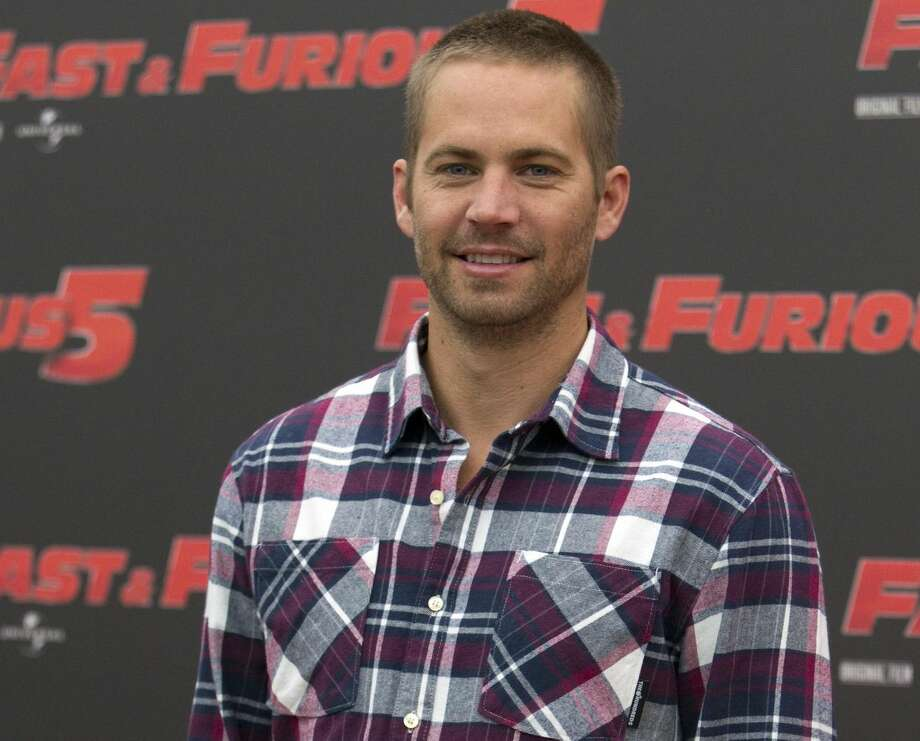 "In this April 29, 2011 file photo, actor Paul Walker poses during the photo call of the movie ""Fast and Furious 5,"" in Rome. Universal Pictures has shut down production on ""Fast & Furious 7"" indefinitely following the death of its star, Walker. The studio announced Wednesday, Dec. 4, 2013, that the film will shut down ""for a period of time so we can assess all options available to move forward with the franchise."" (AP Photo/Andrew Medichini, File)"