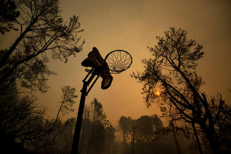 A melted basketball hoop rests in a clearing after the Loma fire tore along a ridge top on Tuesday, Sept. 27, 2016, near Morgan Hill, Calif. More California residents were ordered from their homes Tuesday as a growing wildfire threatened remote communities in the Santa Cruz Mountains. (AP Photo/Noah Berger)