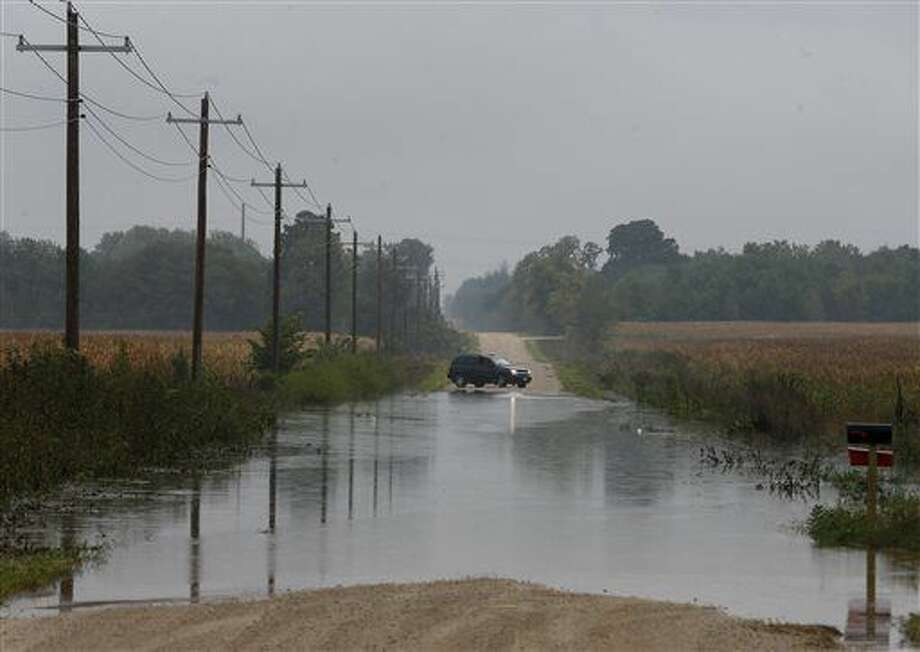 A vehicle turns around as flood waters run over Ford Road, Friday, Sept. 23, 2016 in Cedar Falls, Iowa. Authorities in several Iowa cities were mobilizing resources Friday to handle flooding from a rain-swollen river that has forced evacuations in several communities upstream, while a Wisconsin town was recovering from storms now blamed for two deaths. (Brandon Pollock/The Courier via AP)