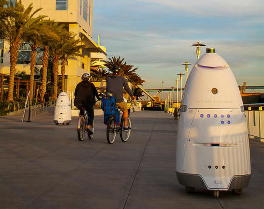 In this April 19, 2016, photo, provided by Stacy Dean Stephens, Knightscope K5 security robots, at right, and background left, patrol alongside a pier, in San Diego. The robots can identify a vehicle parked in a certain location for too long or sense intruders at odd hours. The company expects to have several large mall developers in California start using the robots in late 2016. (Stacy Dean Stephens via AP)