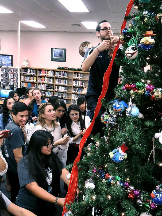 United South High School seniors look on as assistant librarian Ramiro Garza prepares to hang a Christmas ornament on the school's Christmas Tree Friday. The ornaments were designed by the Senior Class 2014 students as part of their traditional senior breakfast and tree decorating ceremony. (Photo by: Cuate Santos