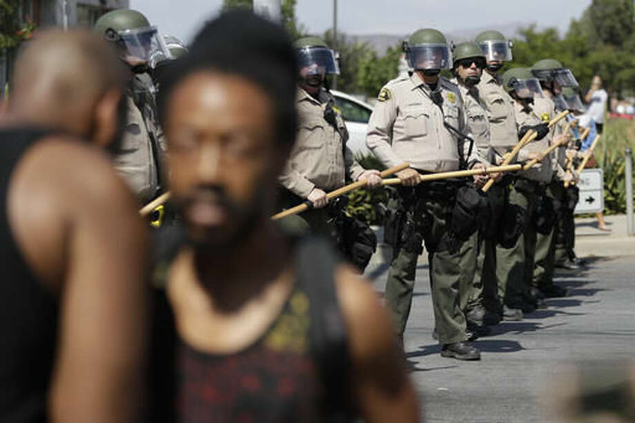 """Police make a formation by a protest Wednesday, Sept. 28, 2016, in El Cajon, Calif. Dozens of demonstrators on Wednesday protested the killing of a black man shot by an officer after authorities said the man pulled an object from a pocket, pointed it and assumed a """"shooting stance."""" (AP Photo/Gregory Bull)"""