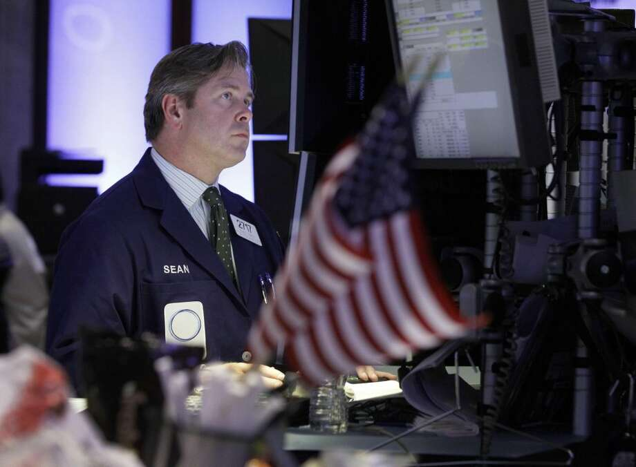 In this Sept. 13, 2012, file photo, specialist Sean O'Brien works at his post on the floor of the New York Stock Exchange. Global stock markets were muted Monday, Sept. 17, as the boost faded from the Federal Reserve's announcement last week of new measures to energize the U.S. economy.(AP Photo/Richard Drew, File)