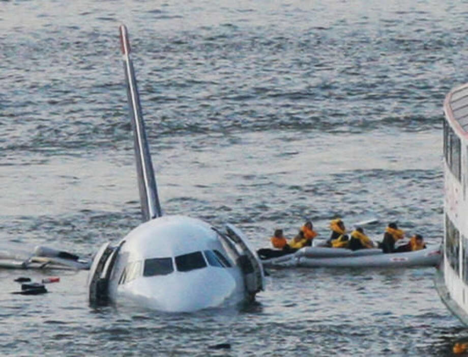 FILE - In this Jan. 15, 2009 file photo, passengers in an inflatable raft move away from an Airbus 320 US Airways aircraft that has gone down in the Hudson River in New York. More than seven years after an airline captain saved 155 lives by ditching his crippled airliner in the Hudson River, now the basis of a new movie, most of the safety recommendations stemming from the accident have yet to be followed. (AP Photo/Bebeto Matthews, File)