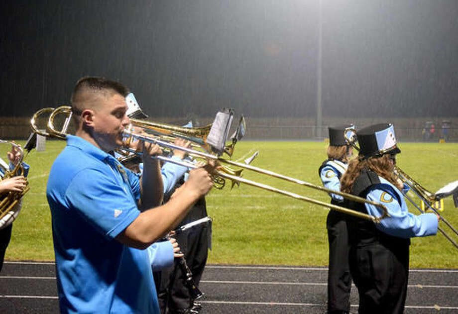 In this Sept. 16, 2016 photo, Cumberland High School Band Director Blake Ozier plays trombone along with his students during a football game Sept. 16, 2016 in Cumberland, Ill. With only 16 students in band this year, Ozier, along with his mother Barb Ozier, a retired band director herself, march along with the students who are more than 40 years her junior to fill in the gaps. (Stan Polanski/Effingham Daily News via AP)