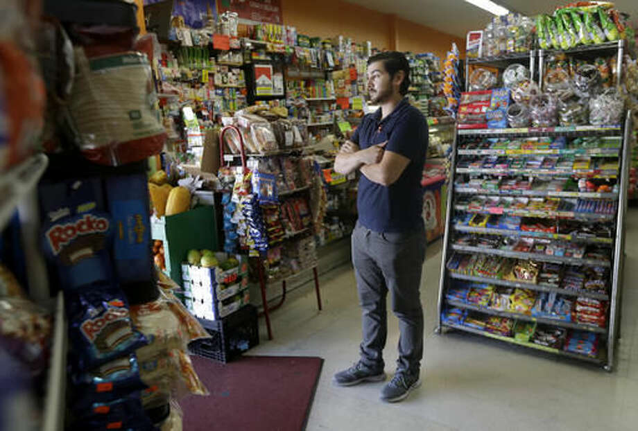 Alex Del Rio stands in the doorway while posing for photos at his family's market El Ahorro in San Francisco, Wednesday, Sept. 21, 2016. In November 2016, voters in San Francisco and Oakland will consider a penny per ounce tax on sugar laden drinks such as bottled cola, sports drinks and iced teas in November. (AP Photo/Jeff Chiu)