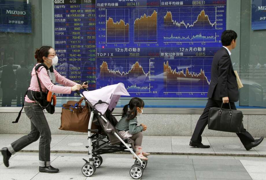 People walk by an electronic stock board of a securities firm in Tokyo, Thursday, June 28, 2012. Good news about the U.S. economy helped Asian stock markets rise Thursday, although lingering fears about Europe's ability to tame its debt turmoil kept gains in check. (AP Photo/Koji Sasahara)