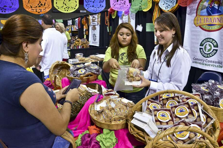 Christina Barron, left, is shown at the Laredo Energy Arena during the 2012 Sister Cities Festival, where she purchased some Mexican candy from Nuevo Leon, Mexico. Attending Barron are, Carolina de Ramos, right and Evelyn Gonzalez. (Cuate Santos/Laredo Morning Times)