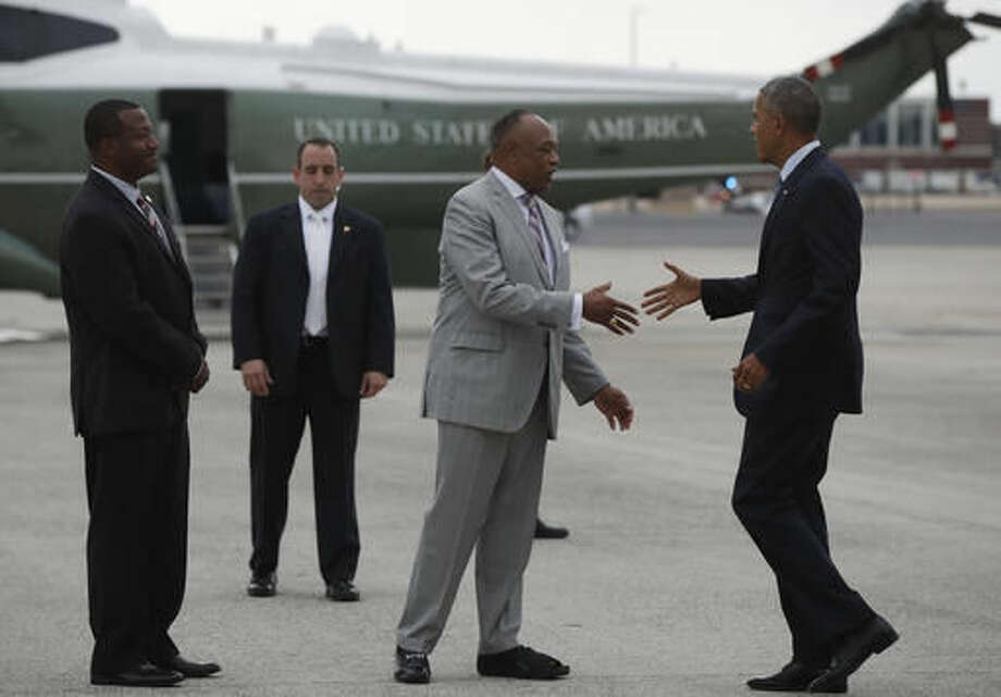 President Barack Obama is greeted by Richmond, Va., Mayor Dwight Jones, and Henrico County, Va. Chairman Tyrone Nelson, as he arrives on Air Force One at Richmond International Airport in Richmond, Va., Wednesday, Sept. 28, 2016, en route to a town hall meeting at Fort Lee. (AP Photo/Carolyn Kaster)