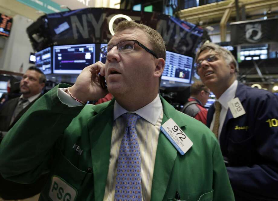 In this Monday, July 29, 2013, file photo, Trader Kevin Coulter, center, works on the floor of the New York Stock Exchange. Global stock markets drifted Wednesday July 31, 2013 as investors waited for the Federal Reserve's latest assessment of the U.S. economy. (AP Photo/Richard Drew, File)