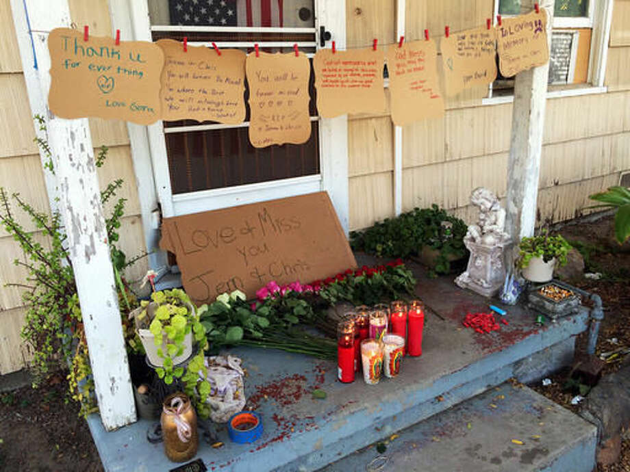 A makeshift memorial is created on the front porch of the home where three adults were found dead Saturday, Sept. 24, 2016, in Fullerton, Calif., Sunday, Sept. 25, 2016. Two men were arrested and a 17-year-old girl was detained Sunday on suspicion of killing the three people inside the Southern California home over the weekend, police said. (AP Photo/Amy Taxin)