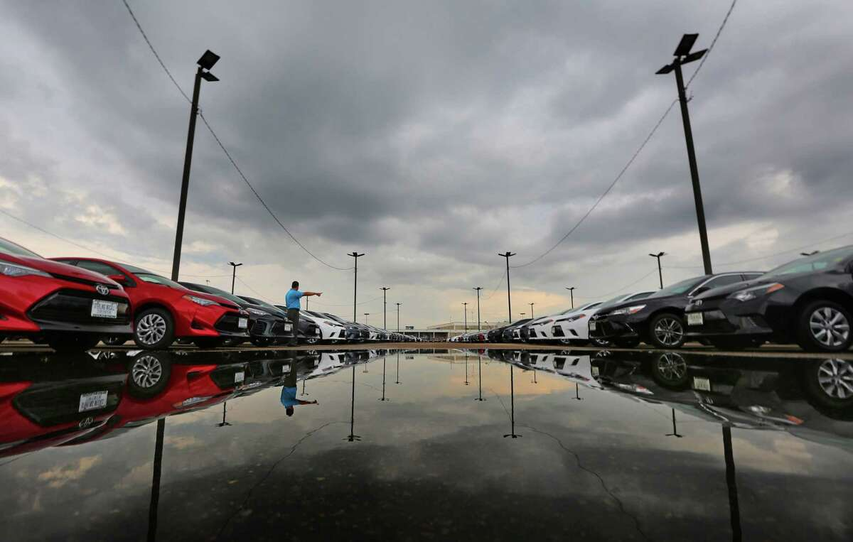 Sales consultant Bhong Zausa points out new Toyotas lined up at Sterling McCall Toyota on the Southwest Freeway.